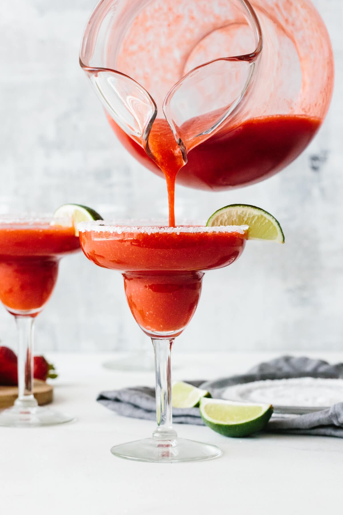 Pouring strawberry margarita into a glass.
