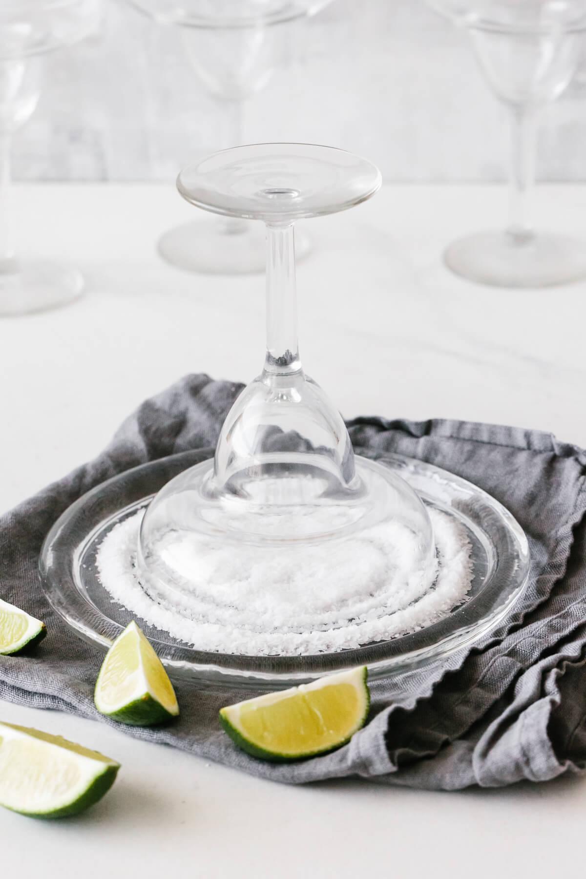Salting the rim of a strawberry margarita glass.