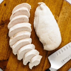 Poached chicken on a cutting board, with one breast sliced up.