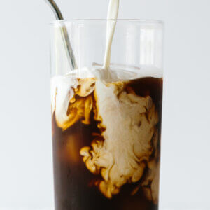 Cold brew coffee in a glass with milk pouring in.