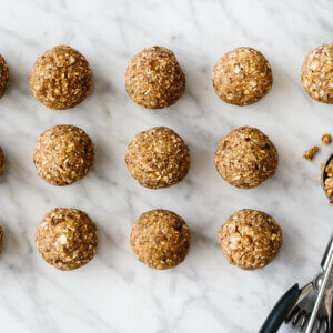 Several energy balls on a counter next to a cookie scoop.