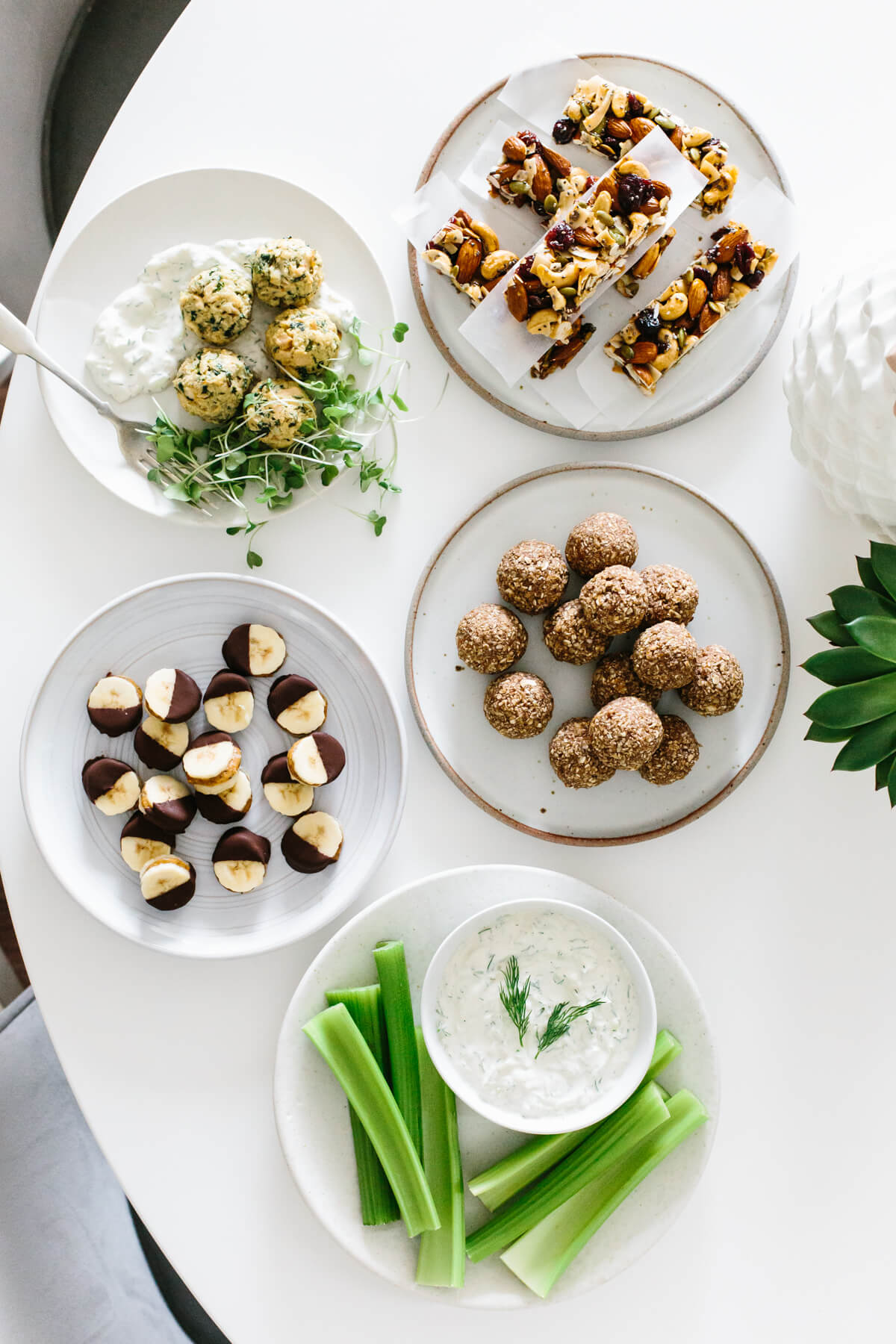 Several healthy snacks and ideas on separate plates on a table.