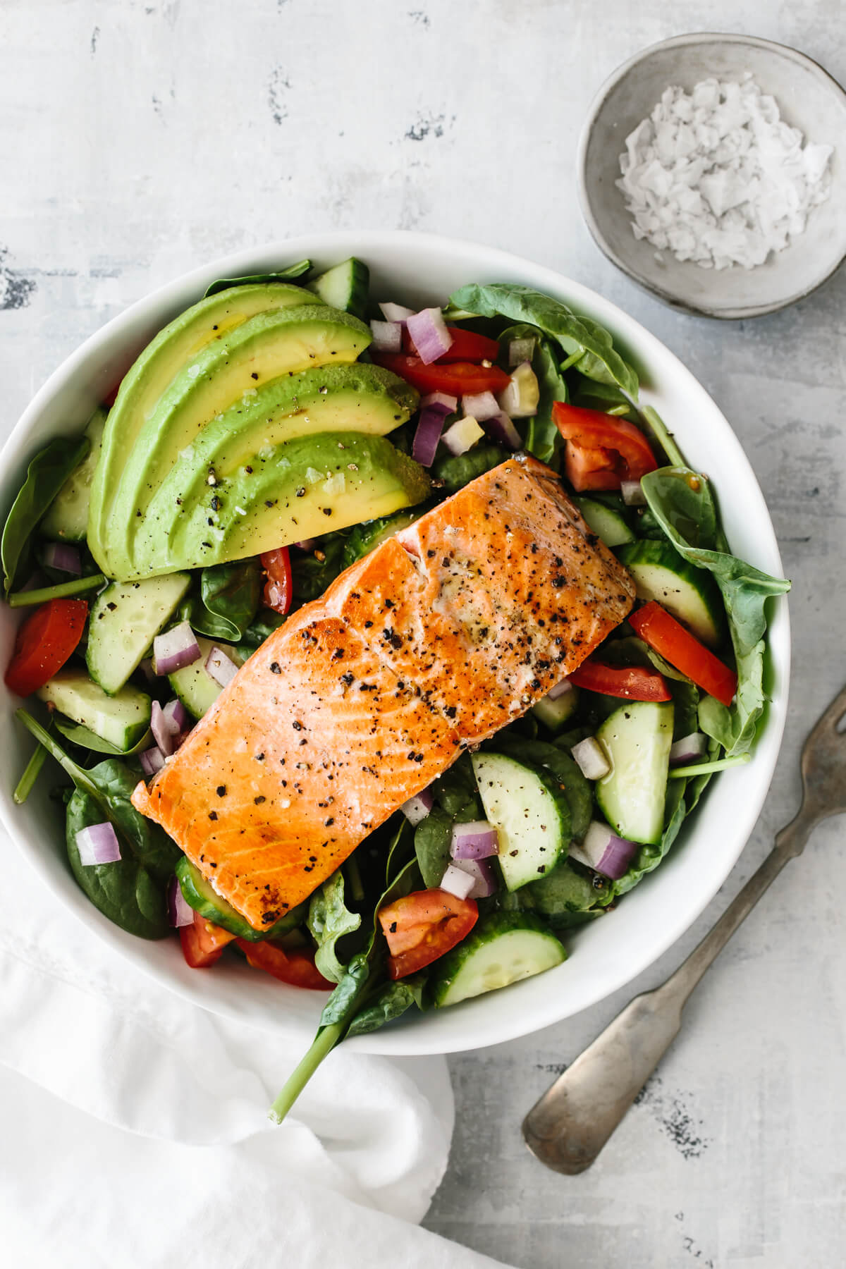 Single salmon fillet on top of salad with avocado and salt pinch bowl off to the side.