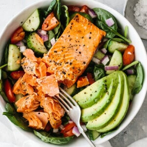 Salmon fillet broken up with fork on top of salad with avocado slices.