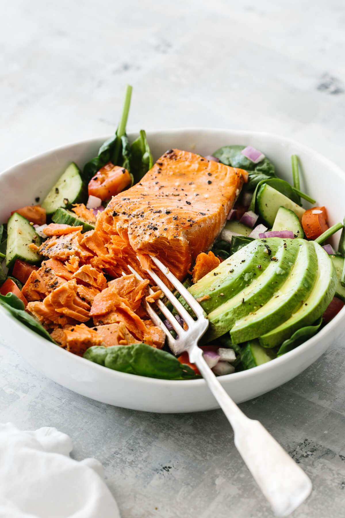 Salmon fillet broken up with fork on top of salad recipe.