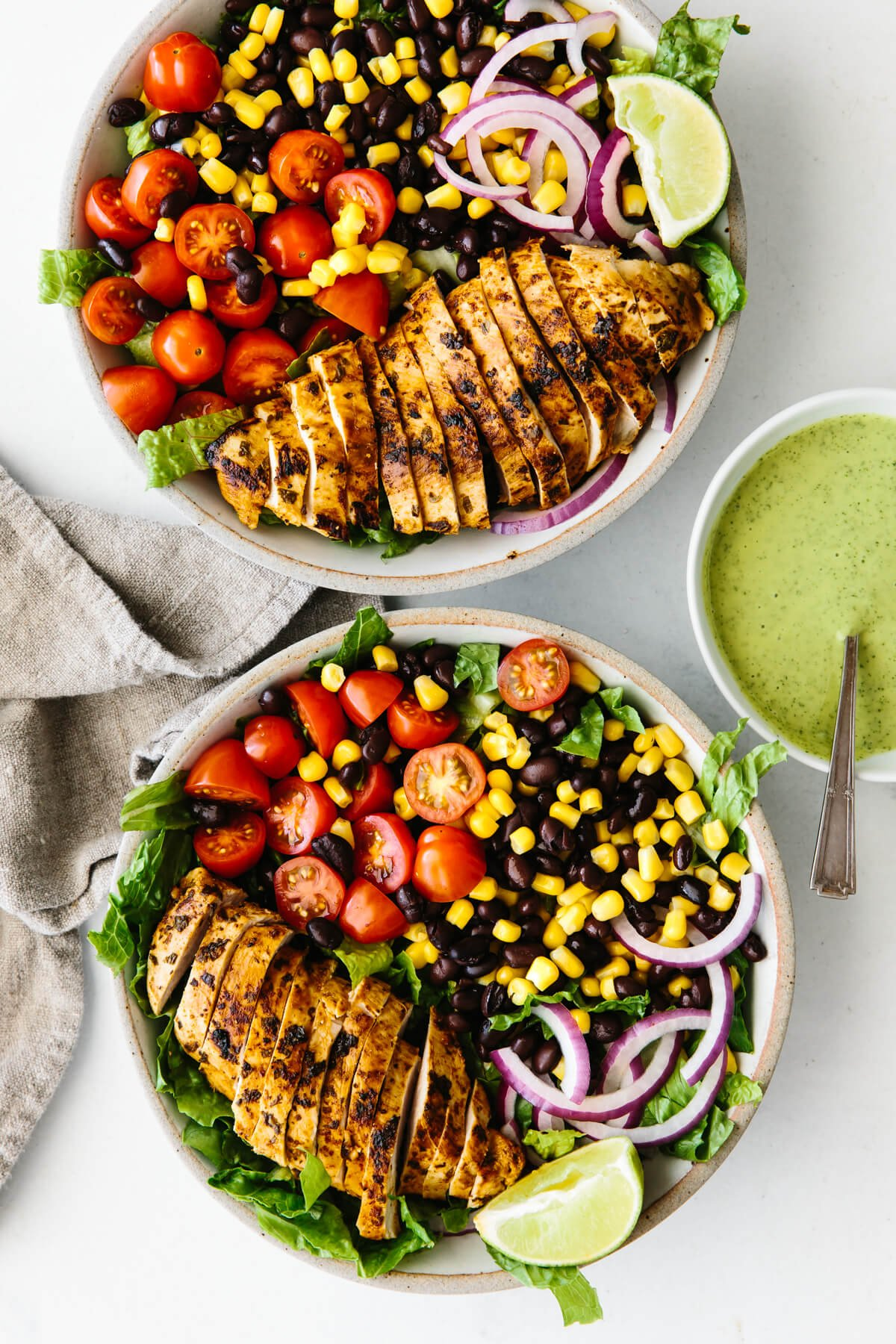 Sliced cilantro lime chicken and southwest salad ingredients in two bowls.