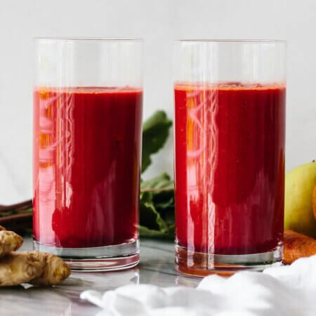 Two glasses of apple carrot beet smoothie next to ingredients.