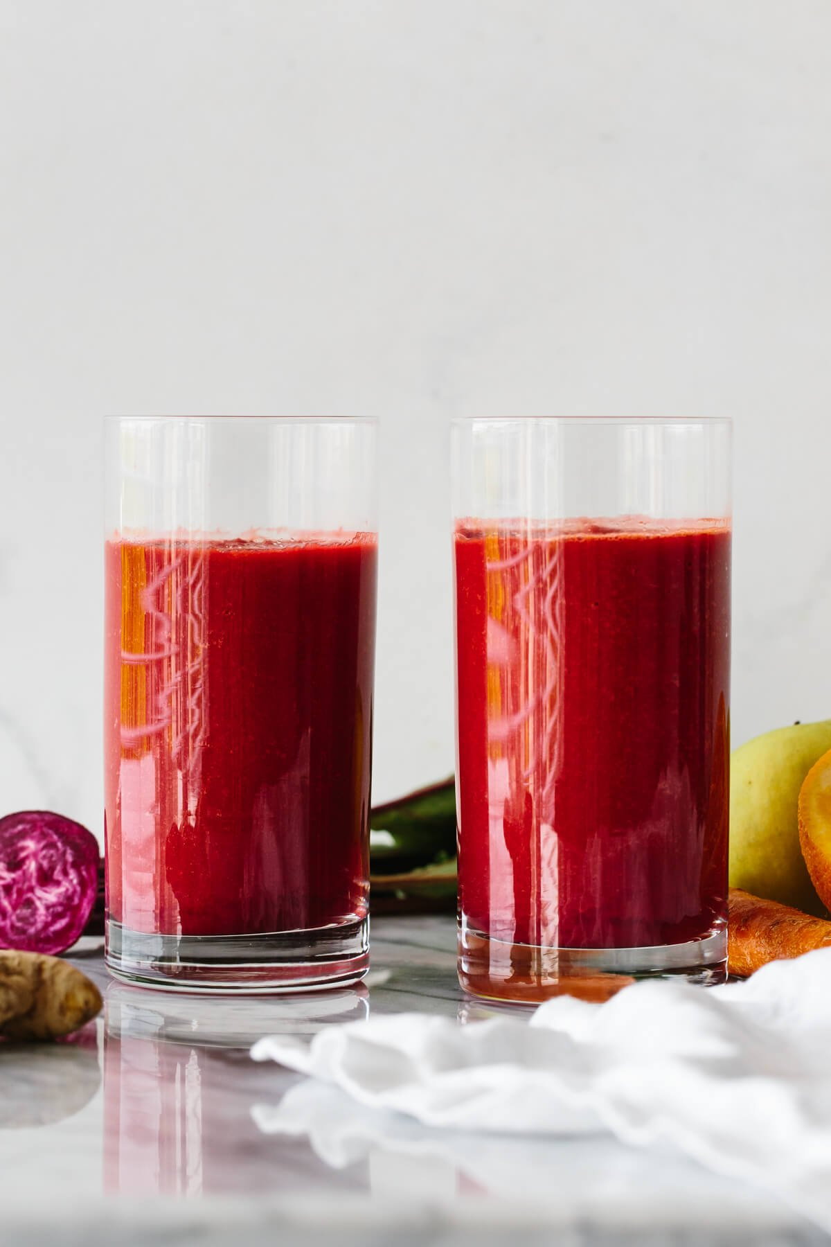 Two glasses of apple, carrot, beet smoothie surrounded by fresh produce.