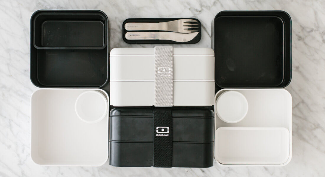 Black and white bento box containers on a countertop.