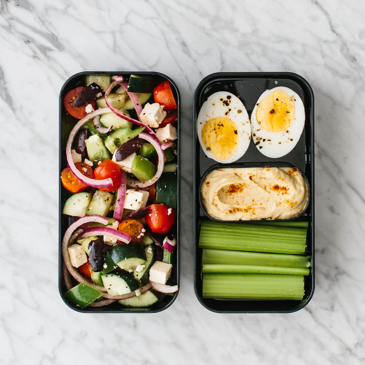 Bento box filled with Greek salad, hard boiled egg, celery and hummus.