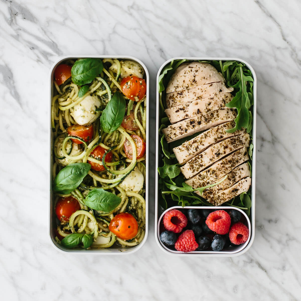 Bento box filled with zucchini noodles, chicken and berries.