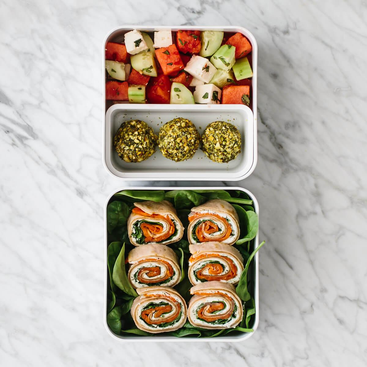Bento box filled with pinwheels, energy balls and fruit salad.