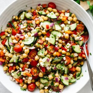 A large white bowl of Mediterranean chickpea salad on a table with parsley leaves.