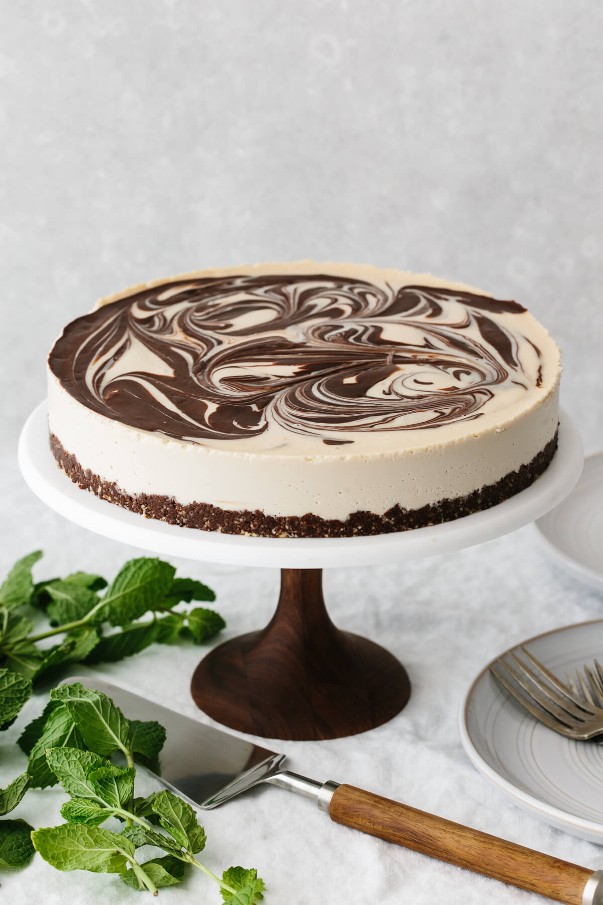 The mint chocolate vegan cheesecake on a cake stand, without toppings.