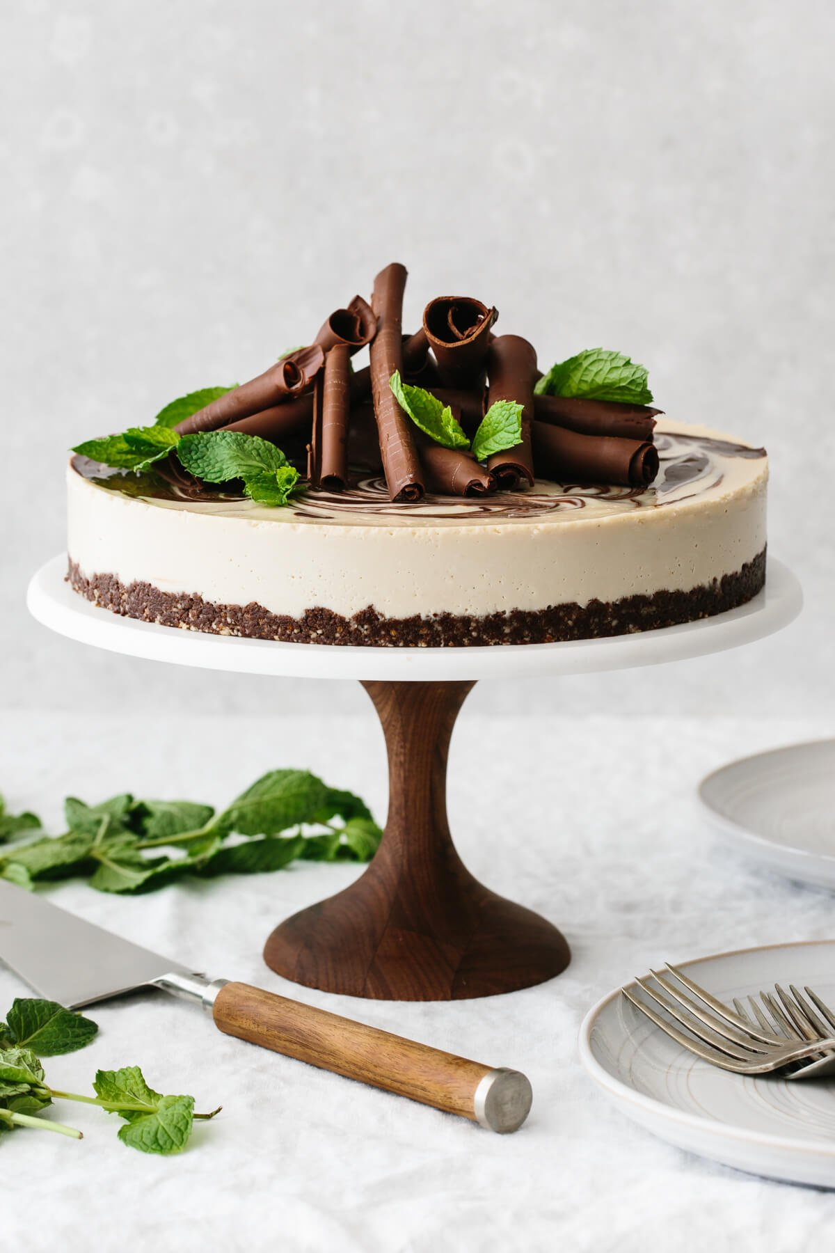 Mint chocolate vegan cheesecake on a cake stand and garnished with chocolate curls and mint leaves.