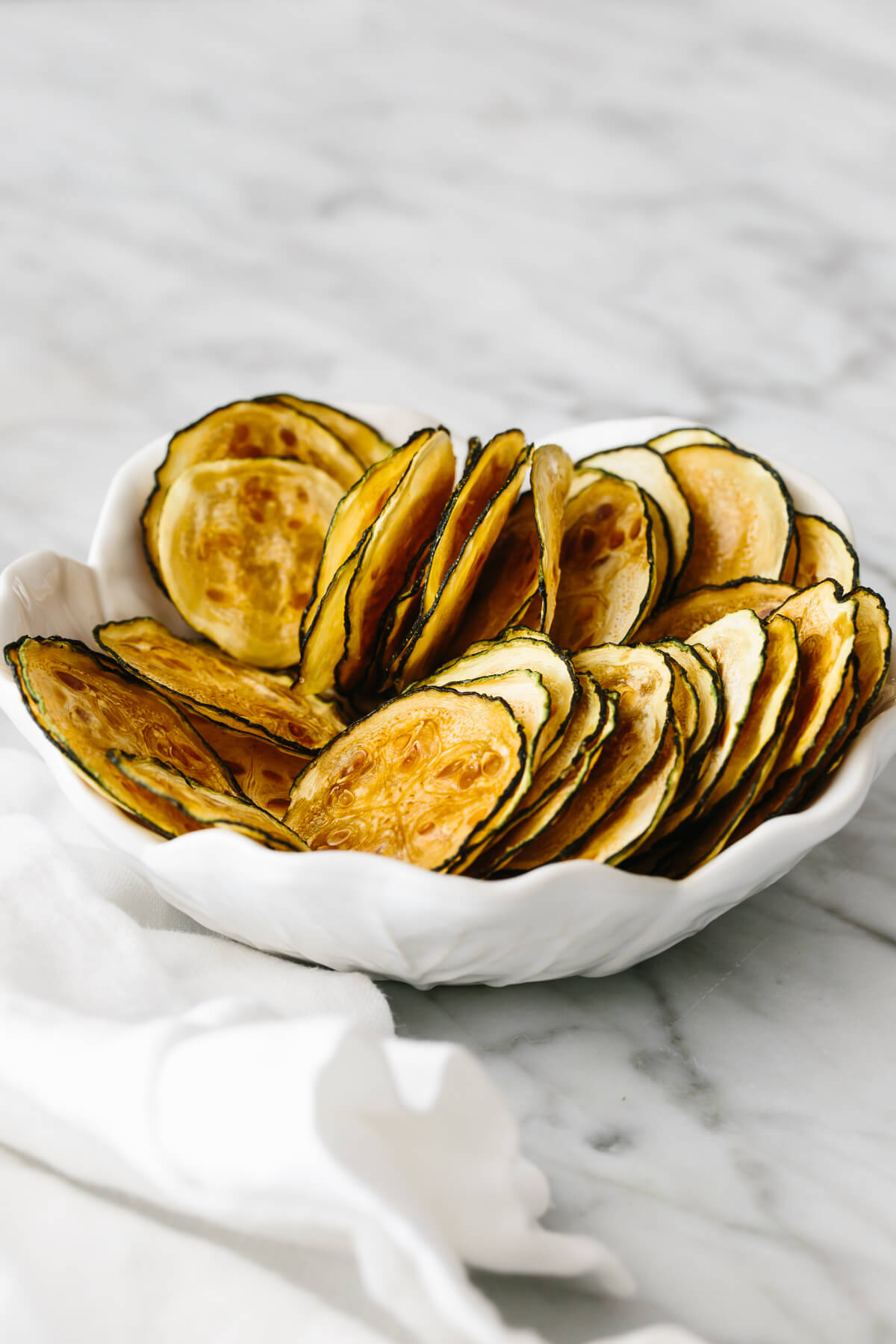 Sliced and baked zucchini chips in a white bowl on a table.
