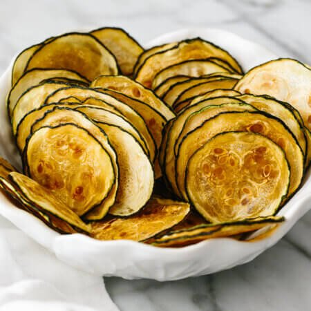 A white bowl holding thinly sliced zucchini chips layered on top of one another.