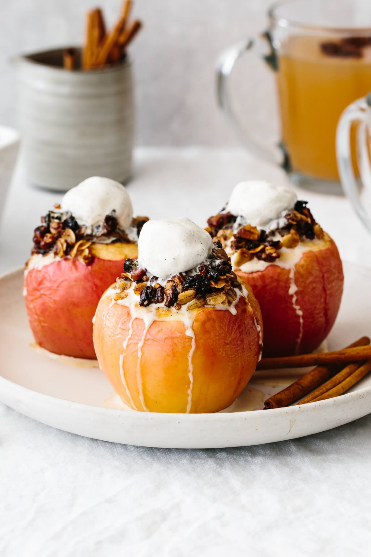 Three baked apples on a plate with melted ice cream on top.