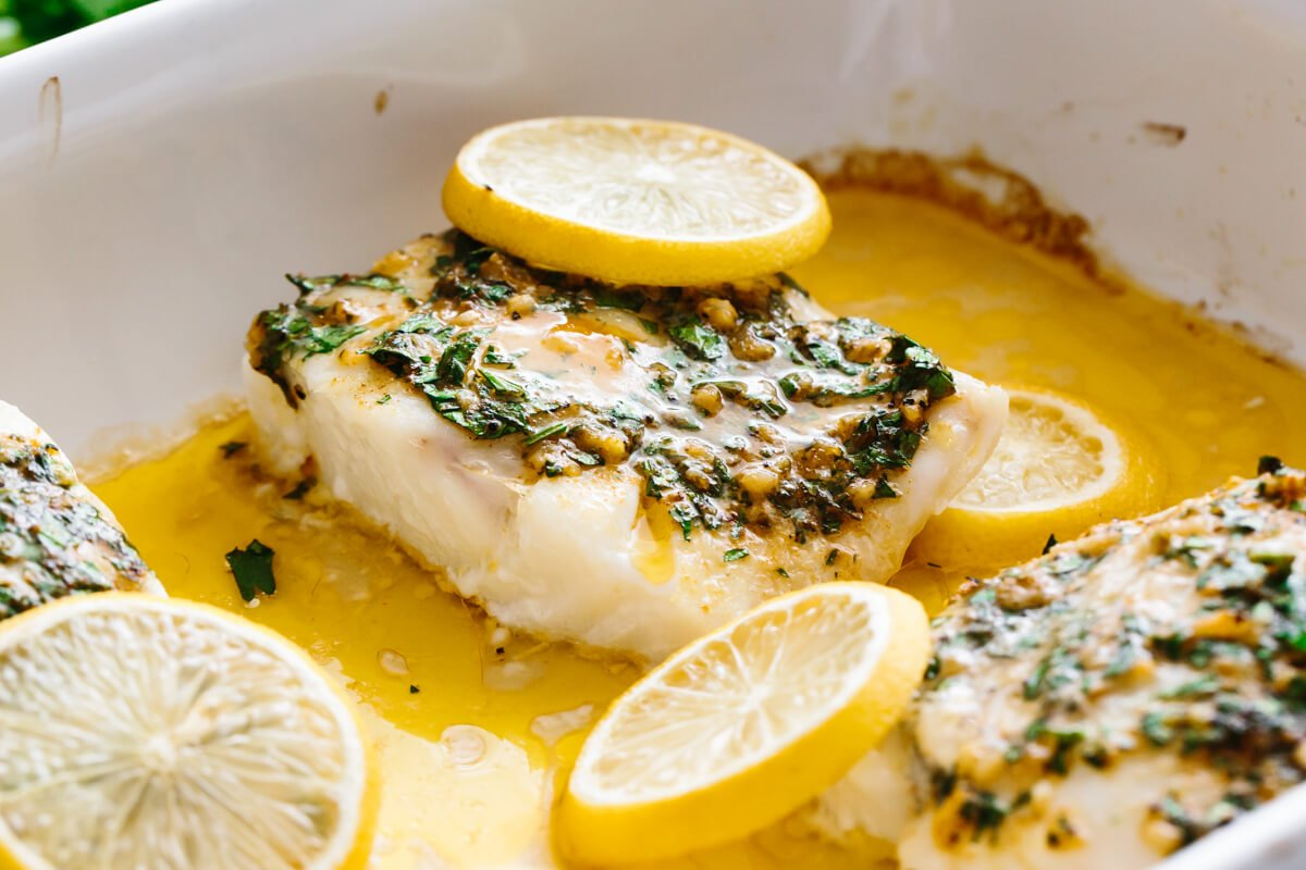 Baked cod filet with lemon slices in a pan.