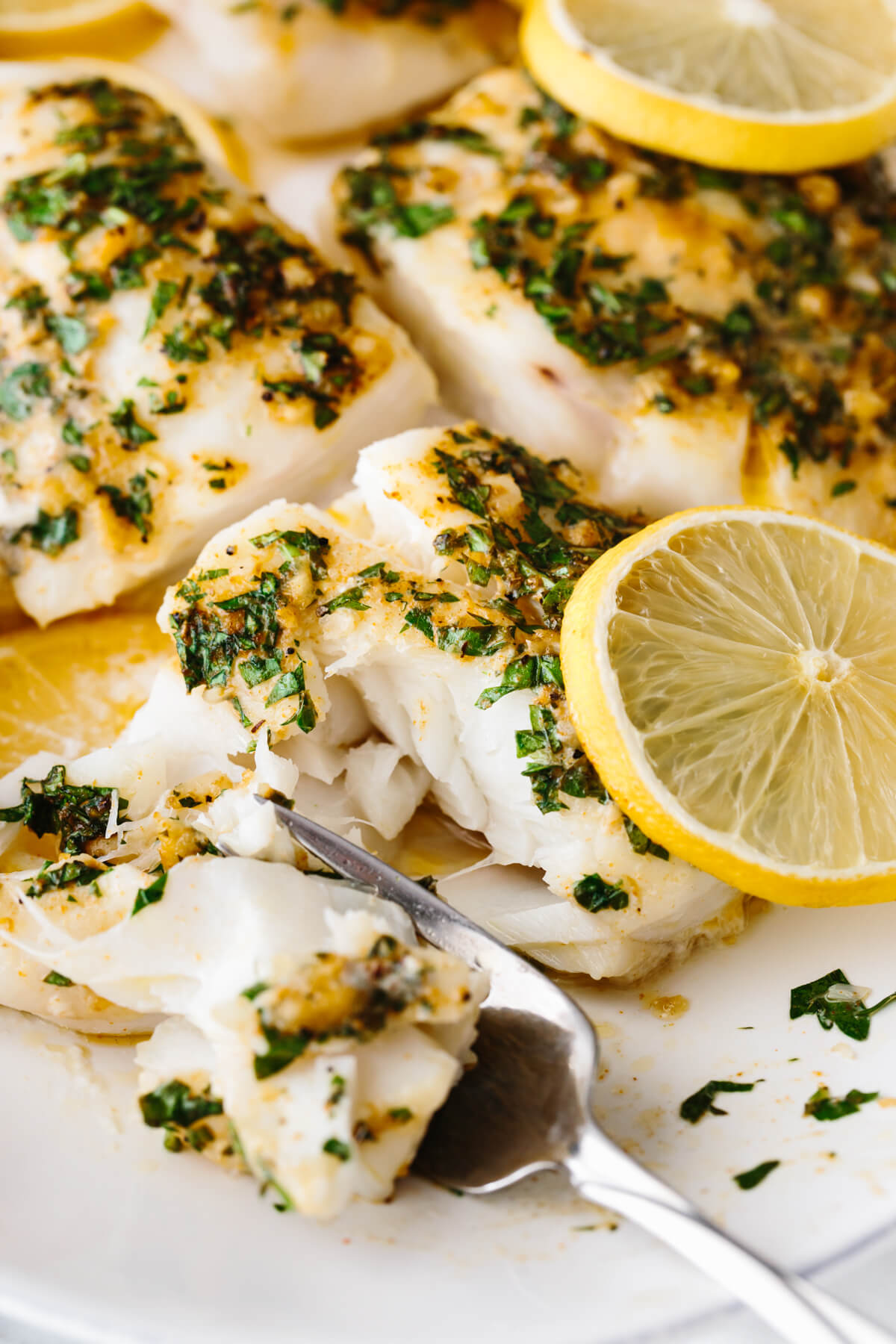 Baked cod filets on a white plate with a fork.