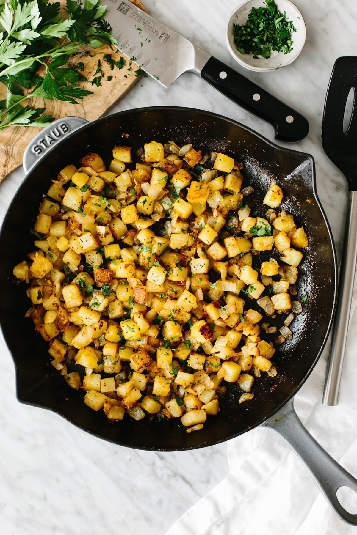 Breakfast potatoes in a skillet on a table.
