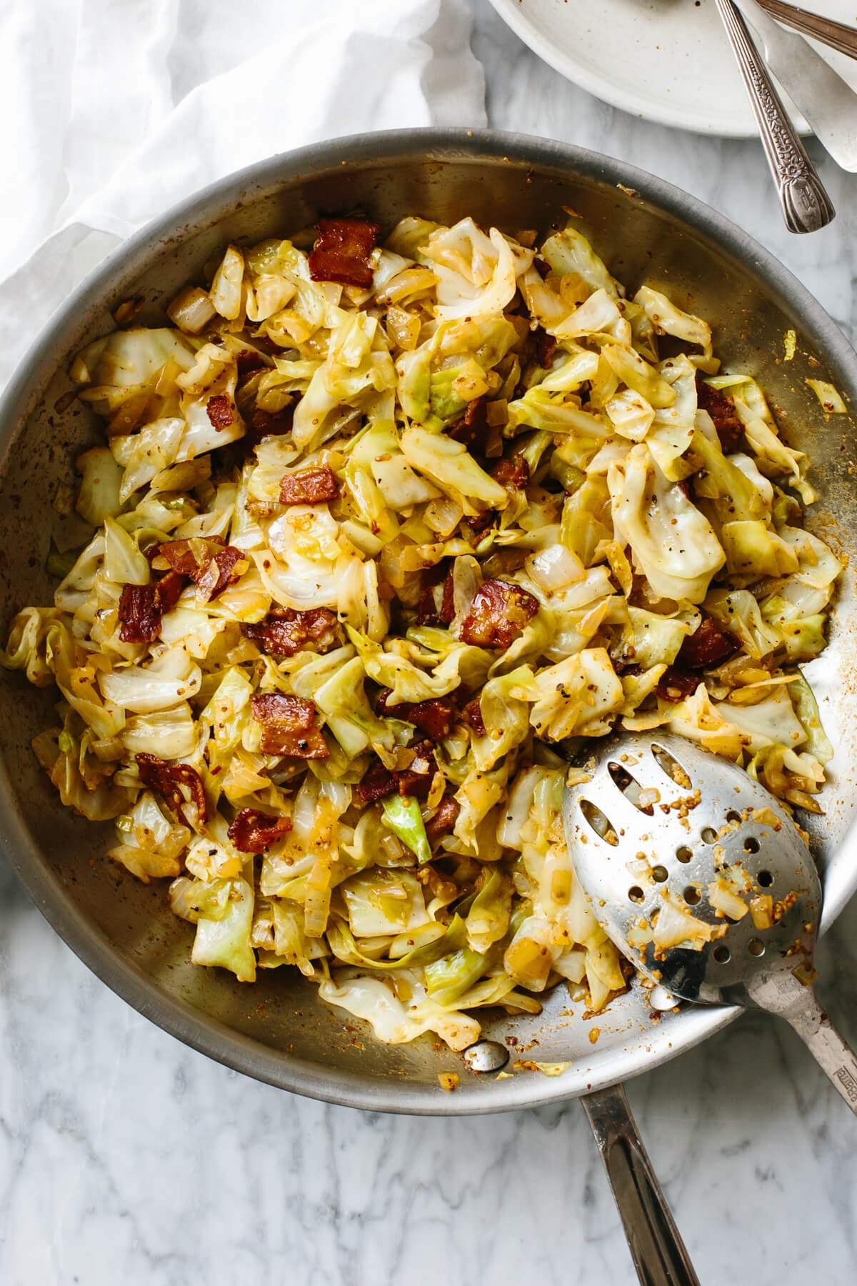Fried cabbage in a pan with a serving spoon on a table.