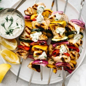 Several Greek chicken kabobs on a plate with lemon wedges and tzatziki sauce.