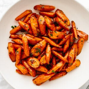 A large white bowl with honey glazed carrots.