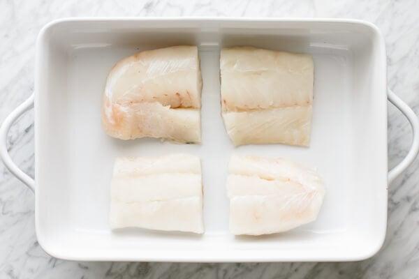 Raw cod filets in a baking dish.