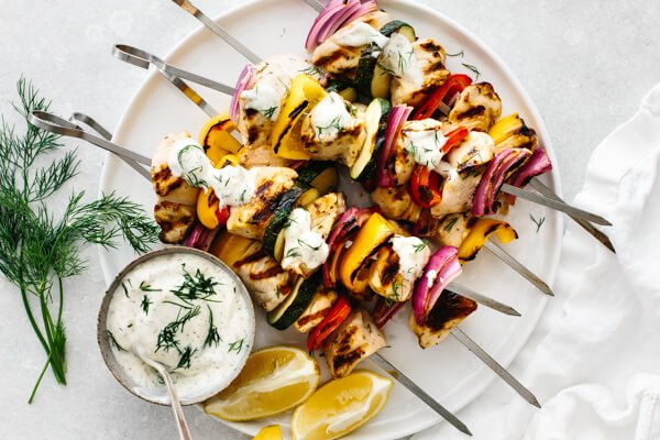 Greek chicken kabobs with lemon wedges on a plate.