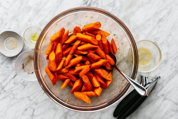Honey glazed carrots being tossed in a glass bowl.