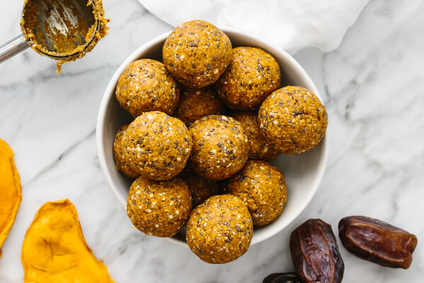 A white bowl filled with mango date energy balls.