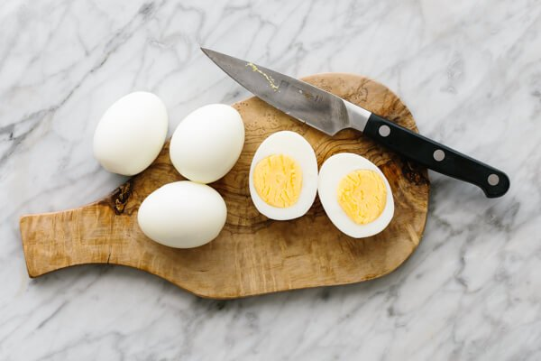 Boiled eggs and sliced boiled eggs on a wooden plate.