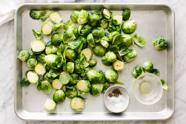 Brussels sprouts being tossed on a sheet pan with seasonings.