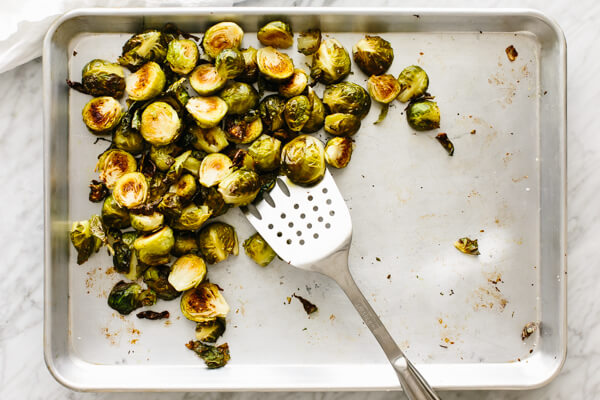 Roasted Brussels sprouts being removed from the sheet pan with a spatula.
