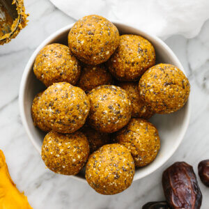 A bowl of mango energy balls next to dates and dried mangos.