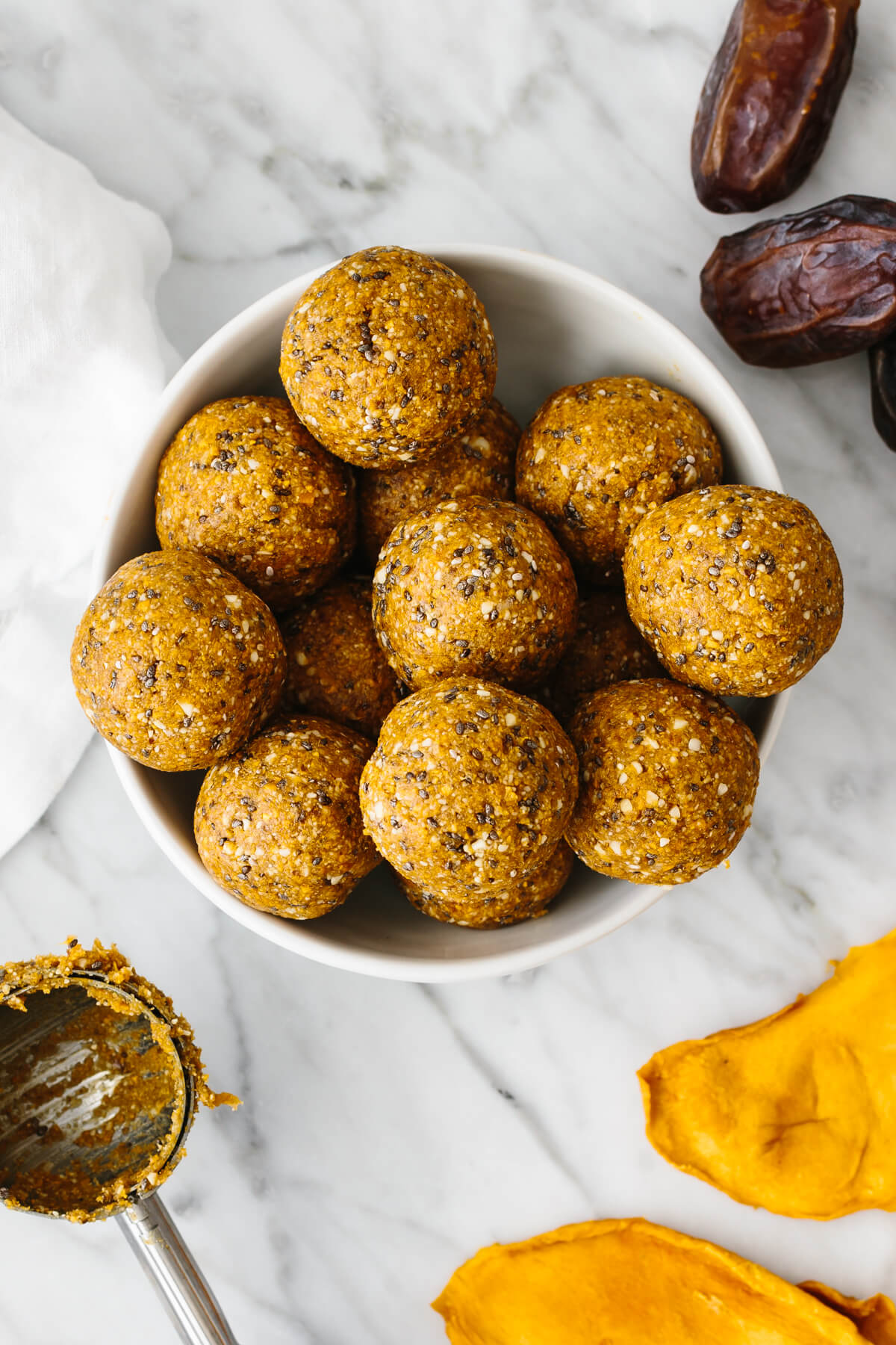 A bowl of mango date energy balls on a table.