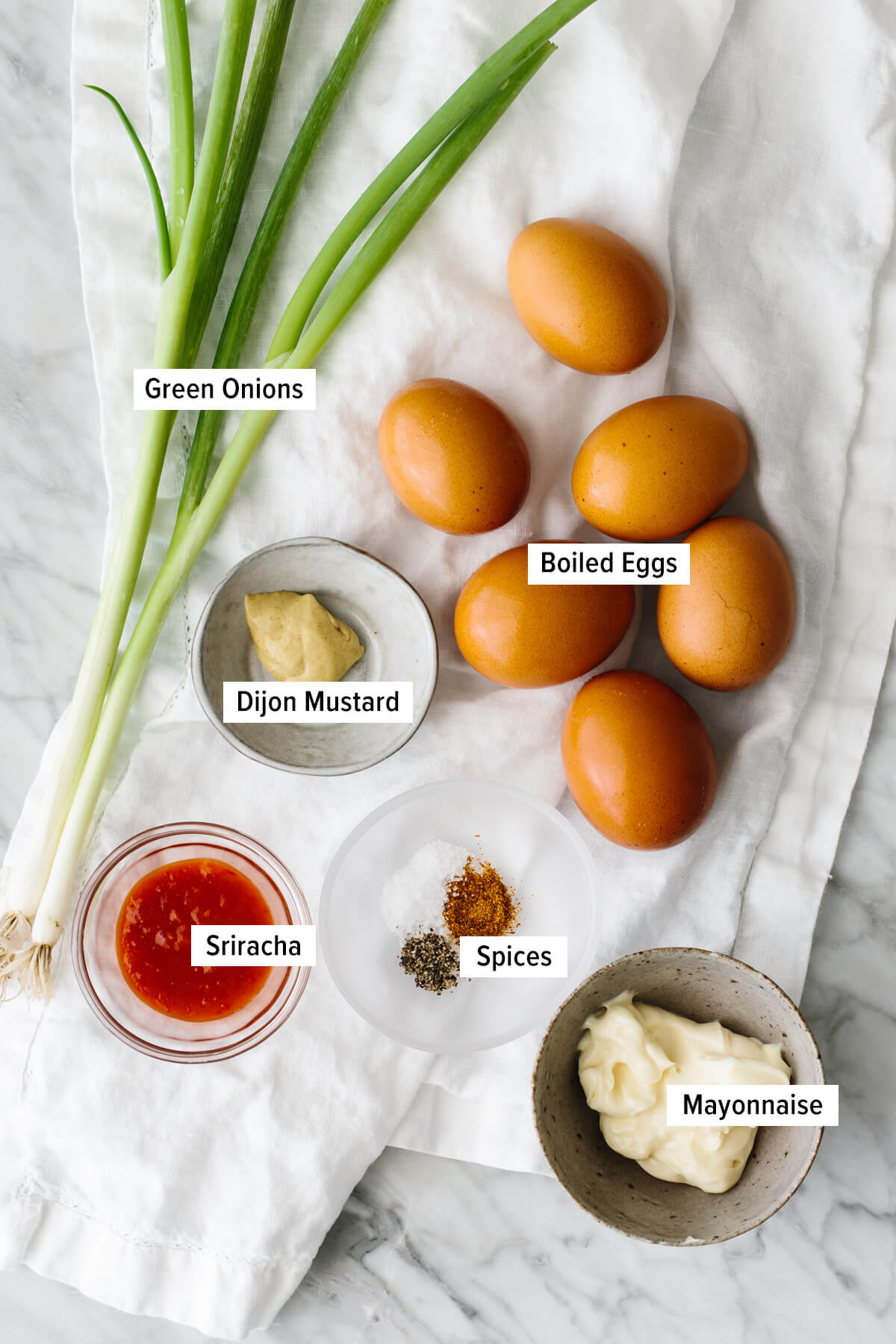 Ingredients for spicy deviled eggs laid out on a table.