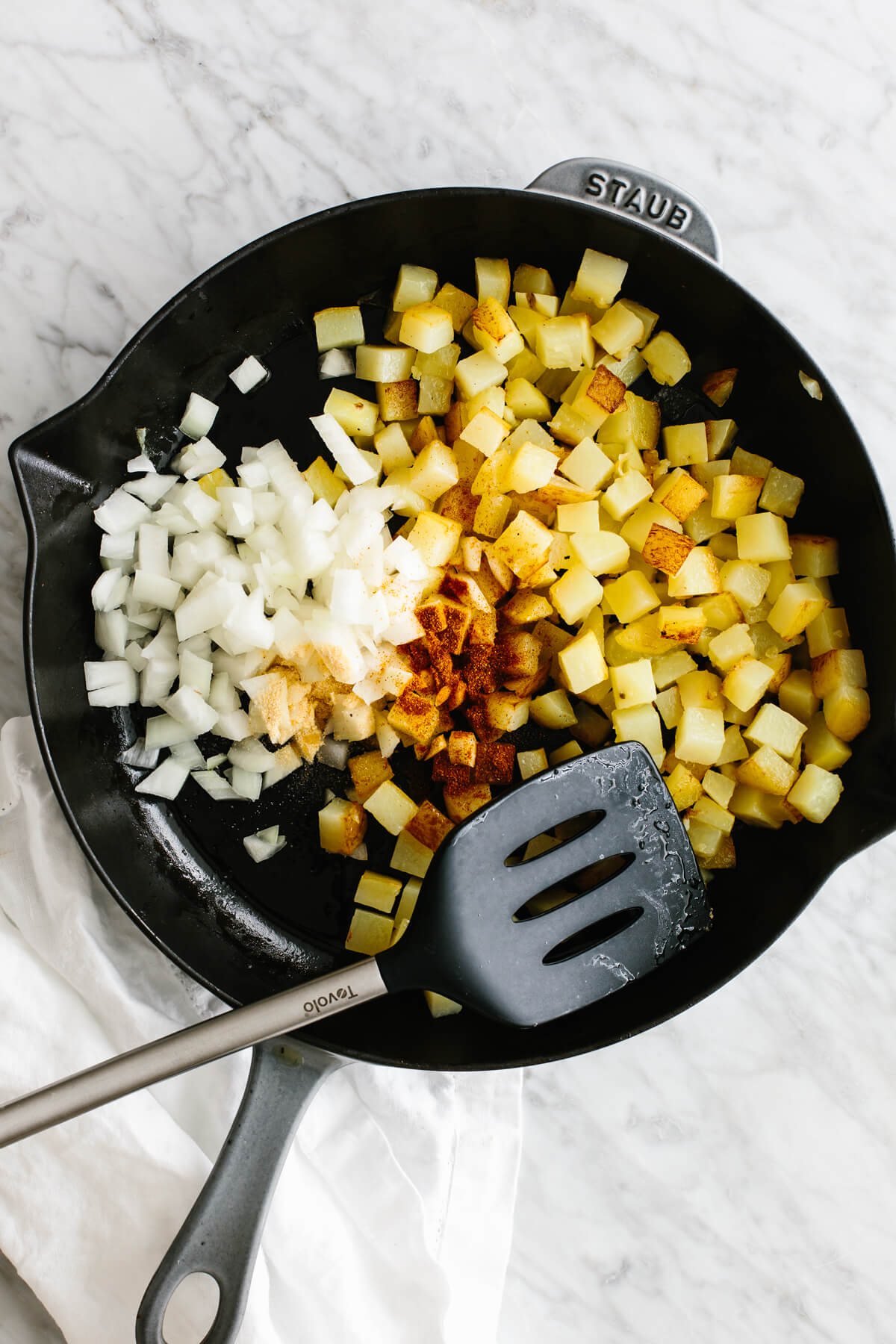 Diced potatoes in a skillet with onion and spices.