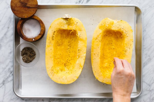 Spaghetti squash being salted and oiled for a side dish.
