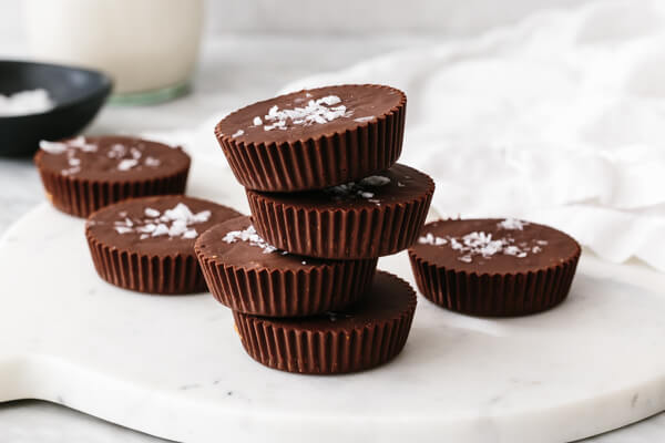 A white board with almond butter cups on top.