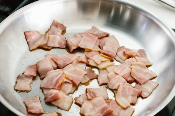 Cooking bacon pieces in a pan.