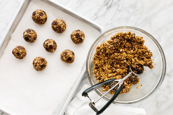 Chocolate chip energy balls next to a bowl with its ingredients.