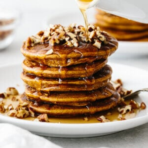 A stack of paleo pumpkin pancakes topped with pecans and maple ginger syrup.