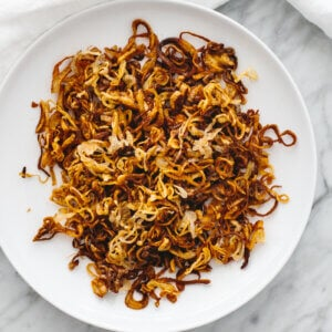 A white plate with crispy shallots.