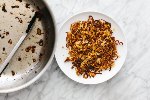 Crispy shallots on a plate next to a pan.