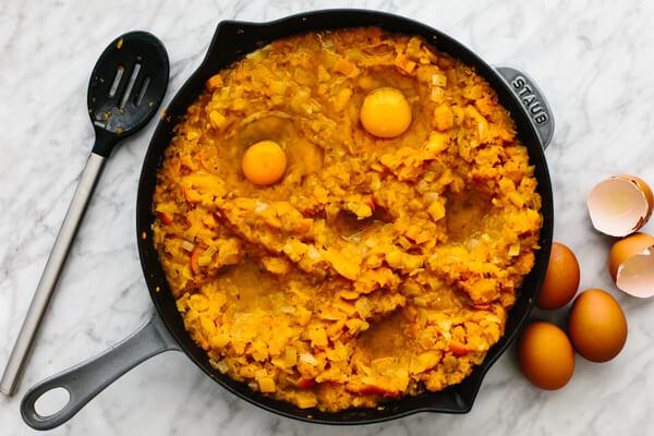 Adding eggs to an orange shakshuka in a skillet.