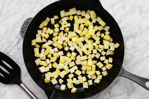 Sauteeing the potatoes in pan.
