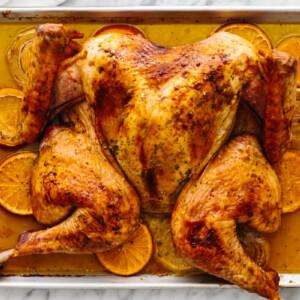 A sheet pan with a maple orange glazed spatchcock turkey.