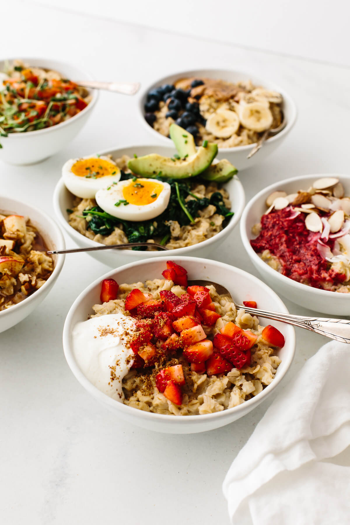 Bowls of oatmeal recipes on a table next to a napkin.
